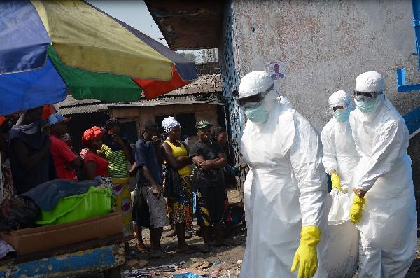 Trabajadores de la Cruz Roja llevan el cuerpo de una persona que murió por Ébola.(AFP).