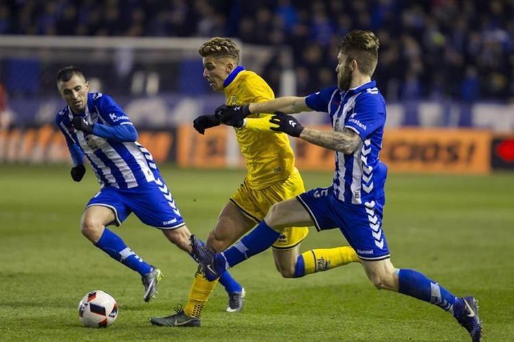 Iván Alejo (c) trata de quedarse con el balón ante los jugadores serbios del Alavés, Nenad Krsticic y Aleksandar Katai. (Foto Prensa Libre: EFE)