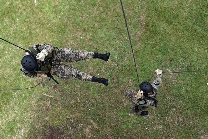 Dos soldados descienden de un helicóptero en una de los entrenamientos después de declarada la guerra a las pandillas. (Foto Prensa Libre: AFP).
