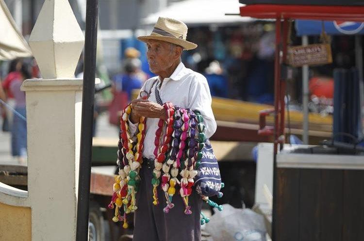 Eladio Jichá, originario de San Martín Jilotepeque, Chimaltenango, ofrece dulces típicos frente a la iglesia de San Juan Bautista. Amatitlán.
