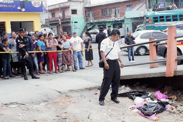 Vecinos de la cabecera de Chimaltenango observan la bolsa plástica donde desconocidos introdujeron el cadáver de un bebé. (Foto Prensa Libre: Víctor Chamalé)