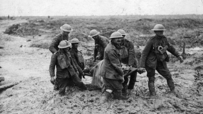 Soldados sacan del lodo a un compañero muerto en combate.