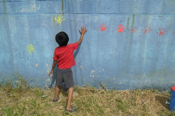 Uno de  los niños de la colonia El Limón plasma sus huellas en un mural dedicado a la paz.