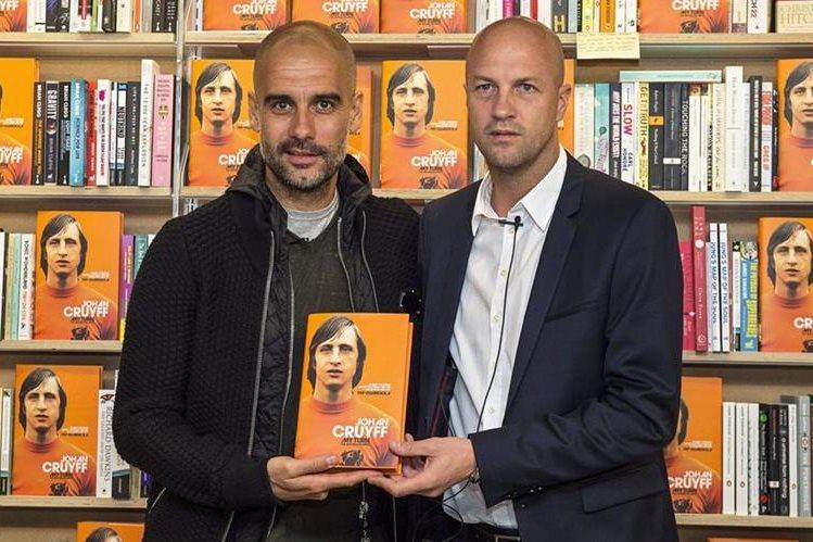El entrenador español del Manchester City, Pep Guardiola (i), y el exfutbolista holandés Jordi Cruyff (d) posan con un ejemplar durante la presentación de la biografía de Johan Cruyff. (Foto Prensa Libre: EFE).