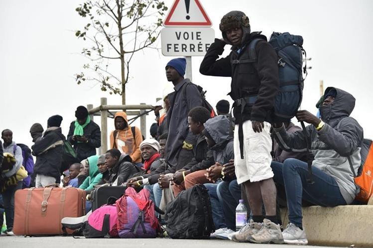Migrantes en Calais esperan el transporte que los llevará a su nuevo refugio. (Foto Prensa Libre: AFP).