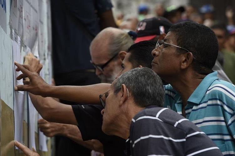 Venezolanos revisan los listados para identificar su urna de votación en una tensa jornada electoral. (Foto Prensa Libre: AFP)