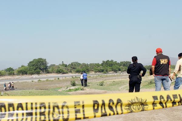 Fiscales del  Ministerio Público recogen evidencias en lugar donde pescadores hallaron el cadáver de un joven, en el río Motagua, en Zacapa. (Foto Prensa Libre: Víctor Gómez)