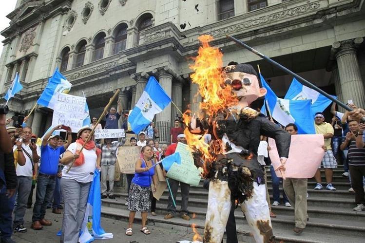Una piñata que simula al presidente Jimmy Morales es quemada frente al Palacio Nacional de la Cultura. (Foto Prensa Libre: Paulo Raquec)