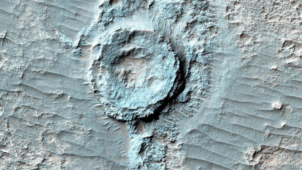 Esta es la imagen de un cráter invertido. Según la NASA, una vez que hizo impacto en Marte, empezó a llenarse con sedimentos que se endurecieron e hicieron más resistentes a la erosión del paisaje alrededor. NASA