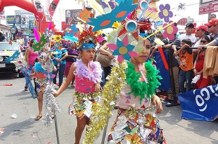 Cinco niñas bailan con trajes de fantasía elaborados con material reciclado.