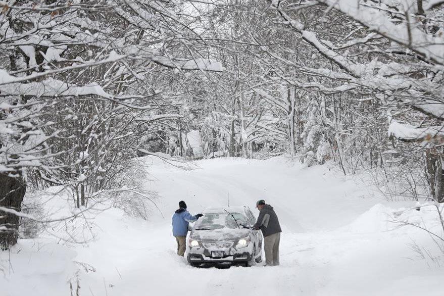 Dos hombres retiran la nieve de un vehículo que quedó varado en la carretera en Grafton, Nueva York. (Foto Prensa Libre: AP).