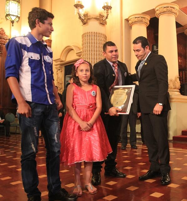 Luis Escalante, padre de Ángel Ariel fallecido en junio del 2015, y sus hermanos, recibieron de manos del presidente Jimmy Morales un placa en memoria del niño que fue víctima de pandilleros. (Foto Prensa Libre: Esbin García)