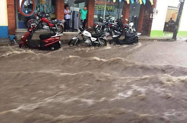 Una motocicleta estacionada fue arrastrada por varios metros por las correntadas. (Foto Prensa Libre: Mario Morales)