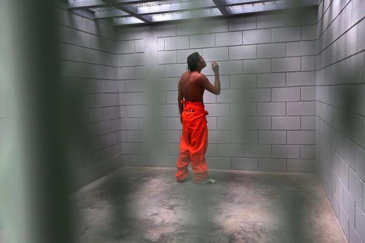 """Un reo observa hacia arriba de su celda, de 2 por 2 metros, en la prisión """"El Pozo"""", ubicada en Santa Bárbara, Honduras. (Foto Prensa Libre: AFP)."""