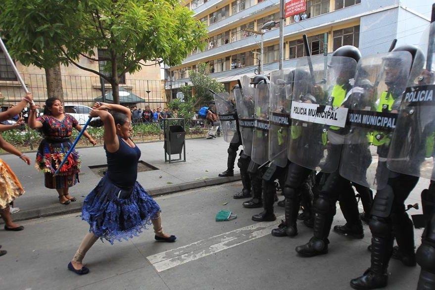 Una vendedora busca con palo agredir a los agentes de la Policía Municipal. (Foto Prensa Libre: Esbin García)