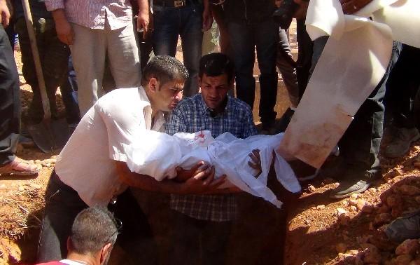 <em>Abdulá Kurdi (cen), padre de Aylan Kurdi, durante el entierro de su hijo en Kobani, Siria.</em>