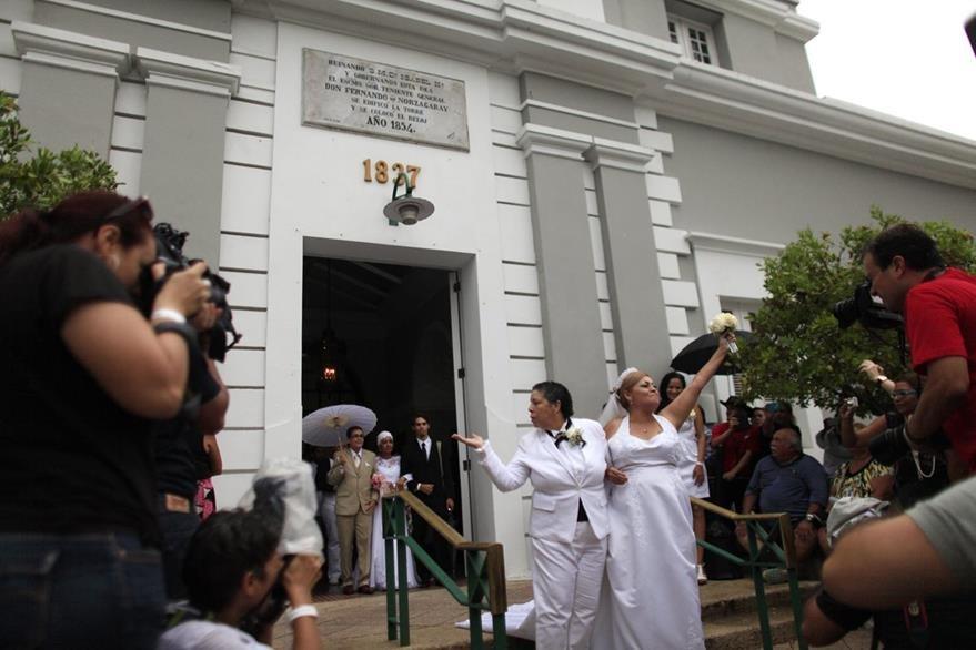 Alma Rosado, izquierda, and Flor Maria Montijo (derecha), saludan a sus conocidos durante la boda gay masiva que tuvo lugar en San Juan, Puerto Rico. (Foto Prensa Libre: AP).
