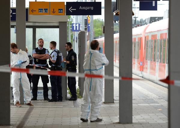 Expertos forenses trabajan frente a un restaurante cerca de la estación de tren.