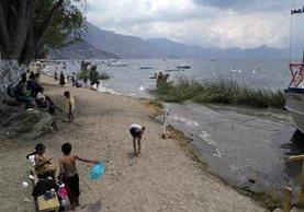 Vecinos y comerciantes recolectan desechos en la playa pública de Panajachel, Sololá. (Foto Prensa Libre: Ángel Julajuj)