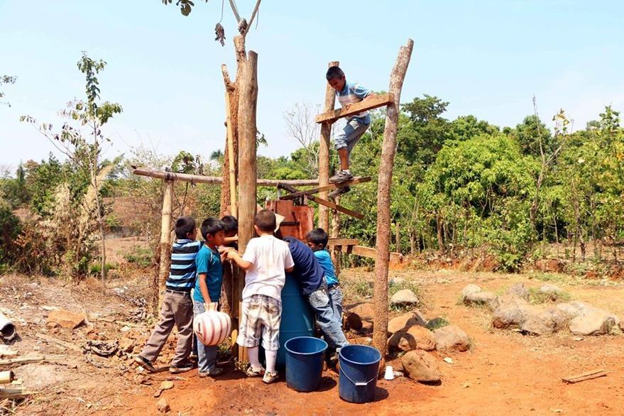 Estudiantes extraen agua  de un pozo para  regarla en el suelo, y así  evitar que  el polvo los afecte. (Foto Prensa Libre: Rolando Miranda).