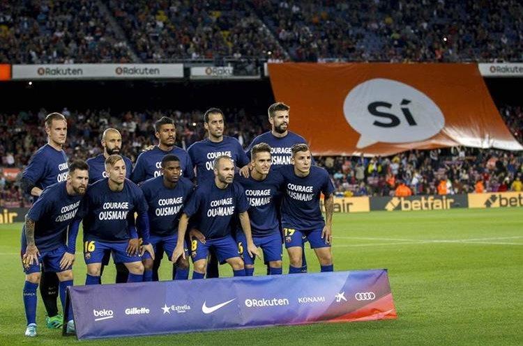 Los jugadores del FC Barcelona posan con camisetas de apoyo a su compañero Ousmane Dembélé.