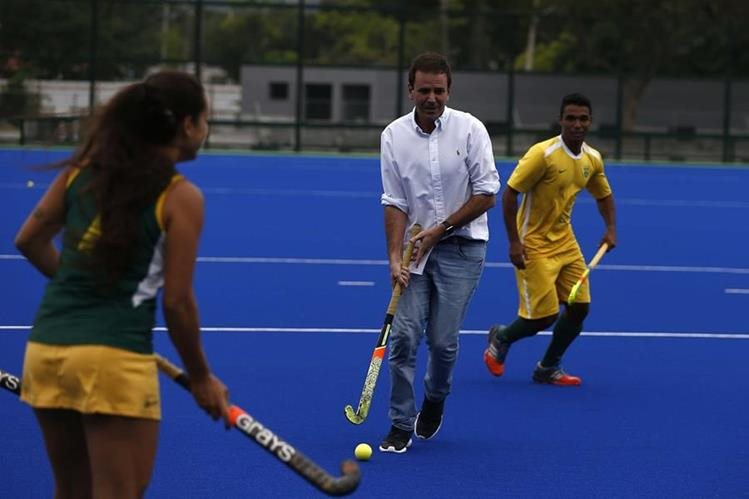 El alcalde de Rio, Eduardo Paes (c), juega con atletas de la selección brasileña de hockey durante una presentación en la cancha del complejo de Deodoro para los Juegos Olímpicos Río. (Foto Prensa Libre: EFE)