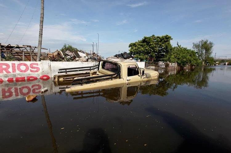 ASU01. ASUNCIÓN (PARAGUAY), 28/12/2015.- Vista de un vehículo cubierto por agua en un barrio de Asunción (Paraguay) hoy, lunes 28 de diciembre de 2015. Por las crecidas de los ríos Paraguay y Paraná, la ciudad del país más castigada por la crecida es Asunción, donde hay unos 90.000 evacuados, según la municipalidad capitalina, aunque la Secretaria de Emergencia Nacional cifra en 70.000 el número de desplazados. La mayoría de esos damnificados viven en espacios proporcionados por el Gobierno desde que comenzara a subir el río, que de momento se mantiene en los 7,8 metros de altura. EFE/Andrés Cristaldo Benítez