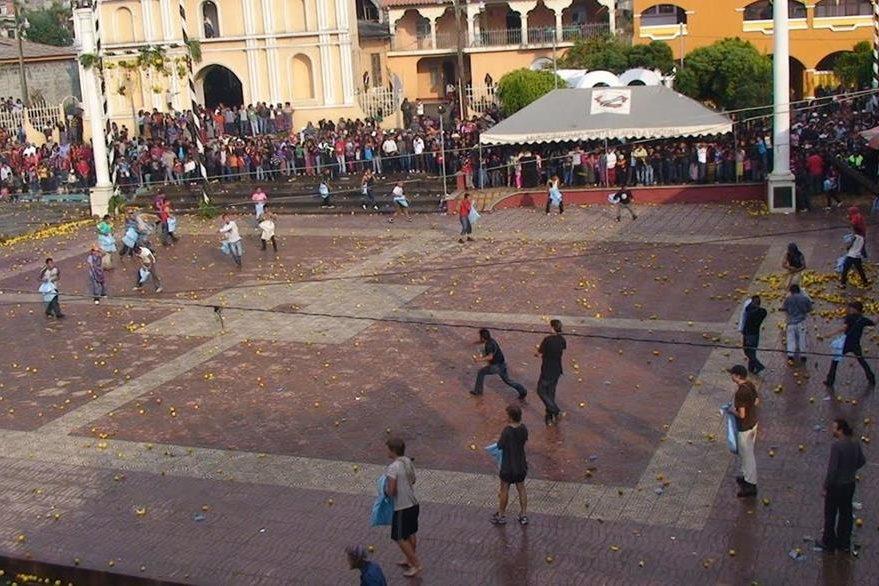 En Santa  Clara La Laguna, Sololá, se desarrolla la  Toronjeada cada Viernes Santo, que forma parte de la penitencia. Dos equipos llenan bolsas o costales con naranjas y se las lanzan entre sí. (Foto Prensa Libre: Ángel Julajuj)