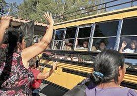 Menores trasladados del Hogar Seguro Virgen de la Asunción se despiden, desde el bus que los transporta, de familiares que llegaron a verificar que se encontraban bien.