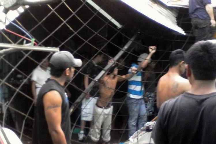 Un grupo de reos de la cárcel para hombres de Jalapa observa los daños en el techo de esa prisión. (Foto Prensa Libre: PNC)