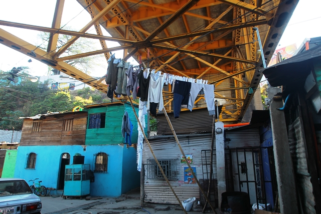 La casa de María, pintada de celeste, se encuentra bajo el puente. Ella y su esposo, Antonio, esperan la noche para vender pollo y papas fritas. (Foto Prensa Libre: Esbin García)