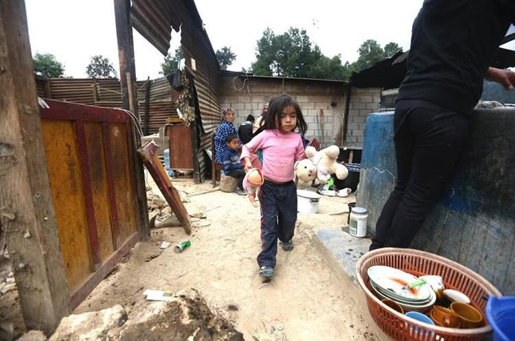 Una niña recoge sus muñecas en el lugar donde estaba la sala de su casa. (Foto Prensa Libre: EFE)