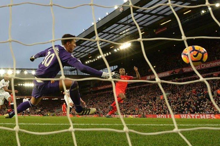 Georginio Wijnaldum hace volar al portero Costel Pantilimon en uno de los goles del Liverpool. (Foto Prensa Libre: AFP)