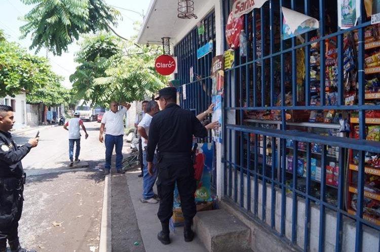Autoridades colocan cartel en una tienda, en el que se señala que está prohibida la venta de bebidas alcohólicas. (Foto Prensa Libre: Enrique Paredes)
