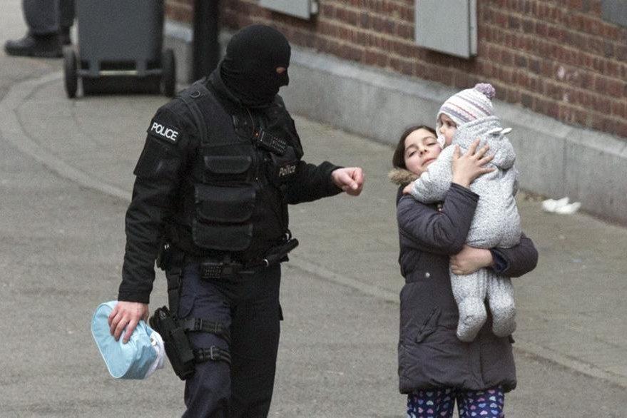 Un policía evacua a una mujer de las cercanías del edificio donde se desató la balacera. (Foto Prensa Libre: AP).