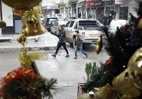 Dos jóvenes sirios caminan en una de las calles del barrio cristiano de Qamishli, donde la celebración de la Navidad ha quedado relegada. (Foto Prensa Libre: AFP).