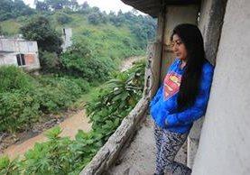 cINDY hERNÁNDEZ observa desde el segundo piso de su vivienda cómo crece el cauce del río Pinula debido a la intensa lluvia. En el 2013 la corriente destruyó el patio trasero y otras casas. (Foto Prensa Libre: Esbin García)