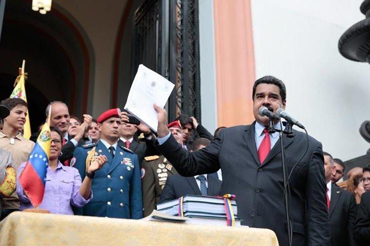 El presidente Nicolás Maduro habla a simpatizantes desde el Palacio de Miraflores mientras sostiene una copia del presupuesto que él aprobó sin consulta del Congreso. (Foto Prensa Libre: EFE).