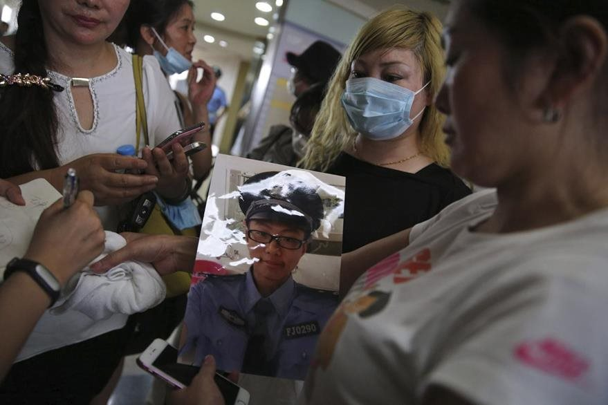 Zhang Yibi sostiene la fotografía de su hijo, un bombero desaparecido, durante su búsqueda en el hospital de Taida. (Foto Prensa Libre: EFE).