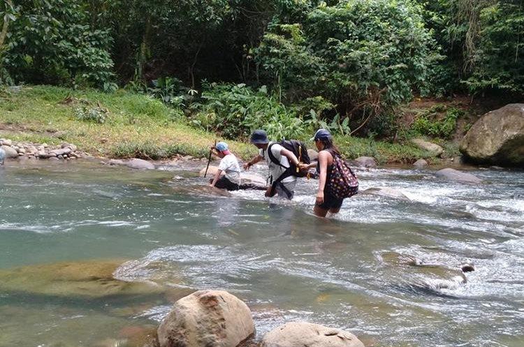 Tres excursionistas atraviesan el río La Puerta que pasa por Malacatán. (Foto Prensa Libre: Whitmer Barrera)