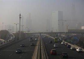 Vehículos circulan por la contaminada ciudad de Pekín, China. (Foto Prensa Libre: EFE).