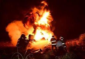 Personas observan a la orilla de la carretera mientras las llamas consumen al camión cisterna. (Foto Prensa Libre: Enrique Paredes)