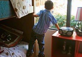 uno de los pequeños, que por ahora carece de una familia, observa por el ventanal de uno de los hogares de protección. Como él, muchos tienen la esperanza de ser elegidos como hijos.