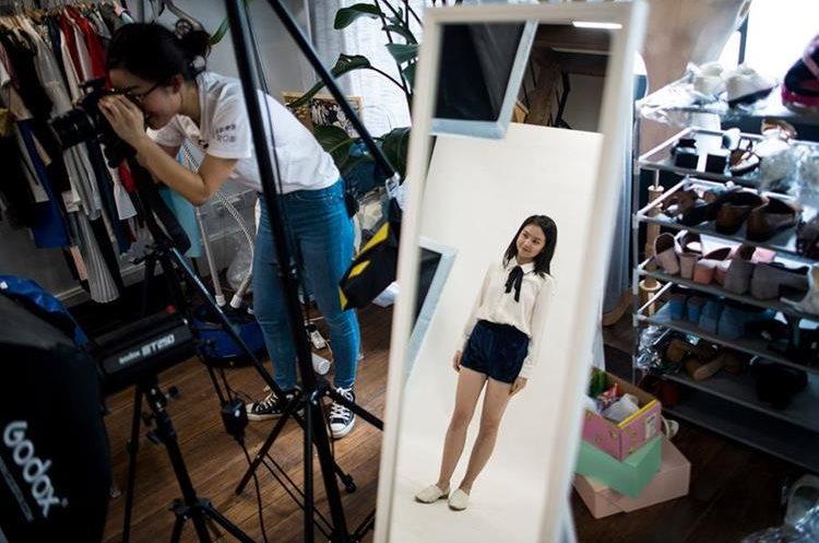 """Este cuadro tomado el 5 de mayo de 2017 muestra a Wang Houhou que toma cuadros de un modelo para el Web site de su e-commerce startup """"gogoand"""" en Shangai. (Foto Prensa Libre: AFP)"""