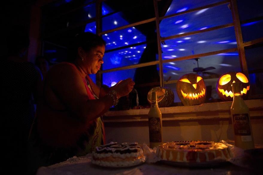La cubana Marilyn Álvarez enciende linternas durante una fiesta de Halloween en su residencia en La Habana, Cuba. (Foto Prensa Libre: AP).