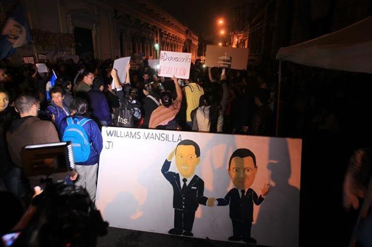 Esta pancarta critica el pago de Q50 mil mensuales que el Ejército hace al Presidente.