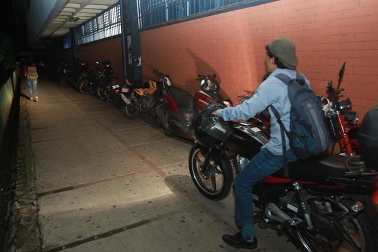 Un estudiante transita con su motocicleta en un área de la Usac donde hay escasa iluminación. (Foto Prensa Libre. Estuardo Paredes)