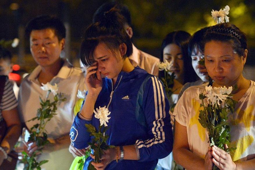 Familiares de las víctimas piden, durante una vigilia, conocer la verdad de lo ocurrido en Tianjin. (Foto Prensa Libre: AFP).