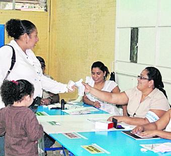 Ciudadanos acuden a emitir su voto, durante la segunda vuelta en las Elecciones Generales 2011. En la imagen una mujer en una mesa de votacion recibe sus documentos.