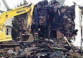 Maquinaria remueve los escombros del lugar donde ocurrió la tragedia. (Foto Prensa Libre: AP).